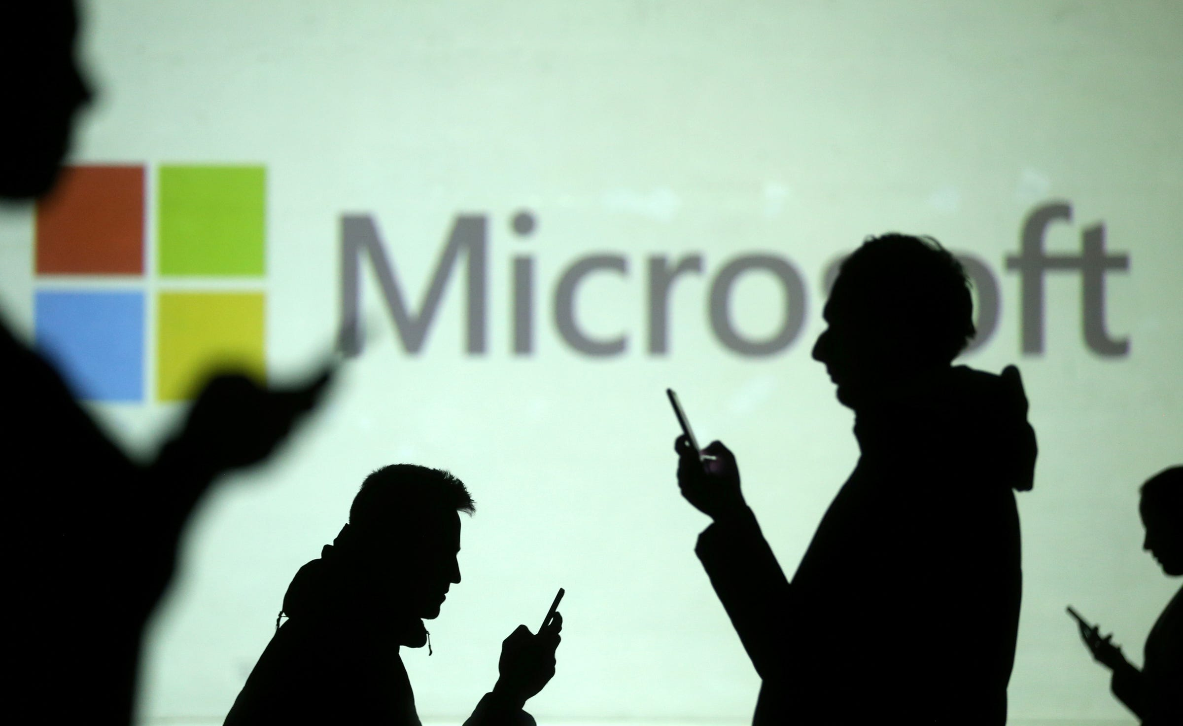 FILE PHOTO: Silhouettes of mobile users are seen next to a screen projection of Microsoft logo in this picture illustration taken March 28, 2018. REUTERS/Dado Ruvic/Illustration
