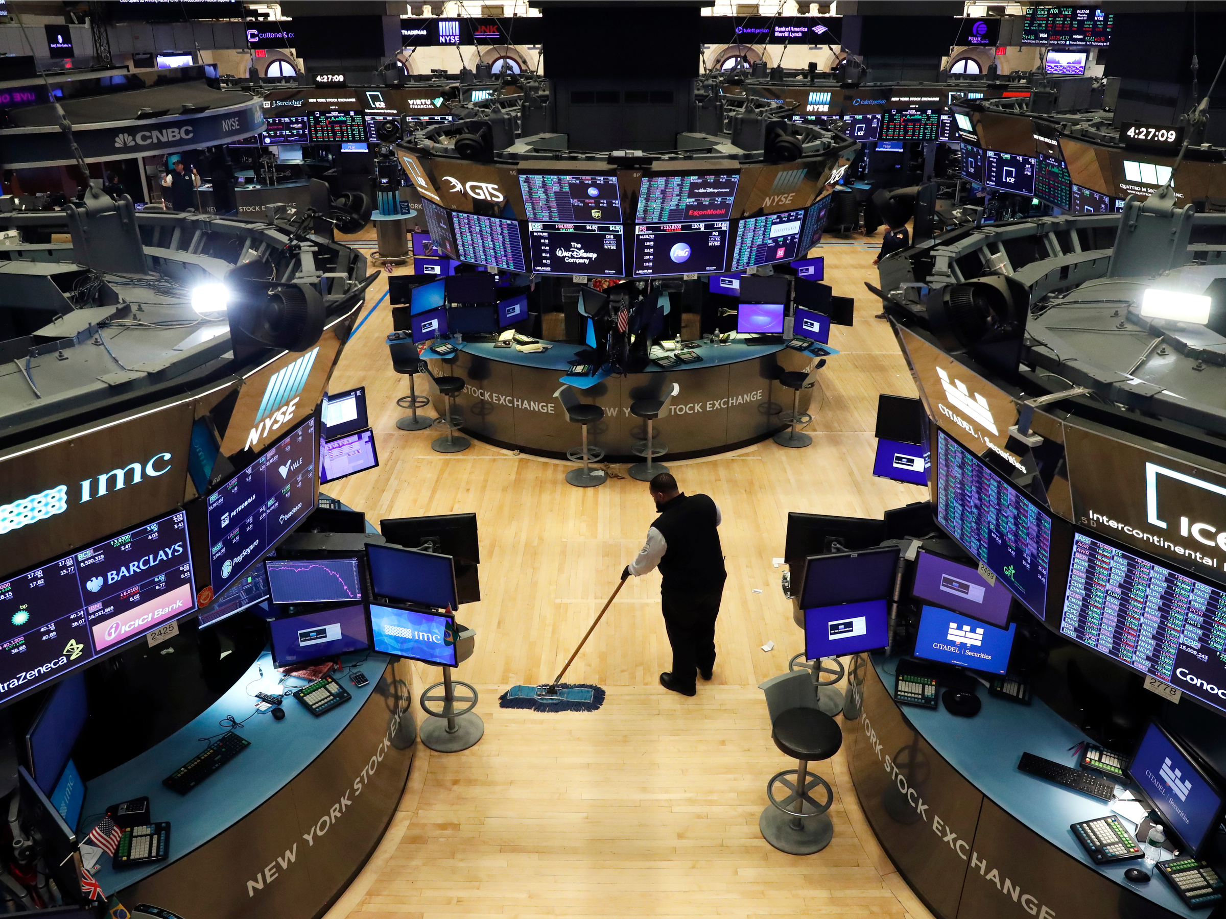 A man cleans up on the trading floor, following traders testing positive for Coronavirus disease (COVID-19), at the New York Stock Exchange (NYSE) in New York, U.S., March 19, 2020.