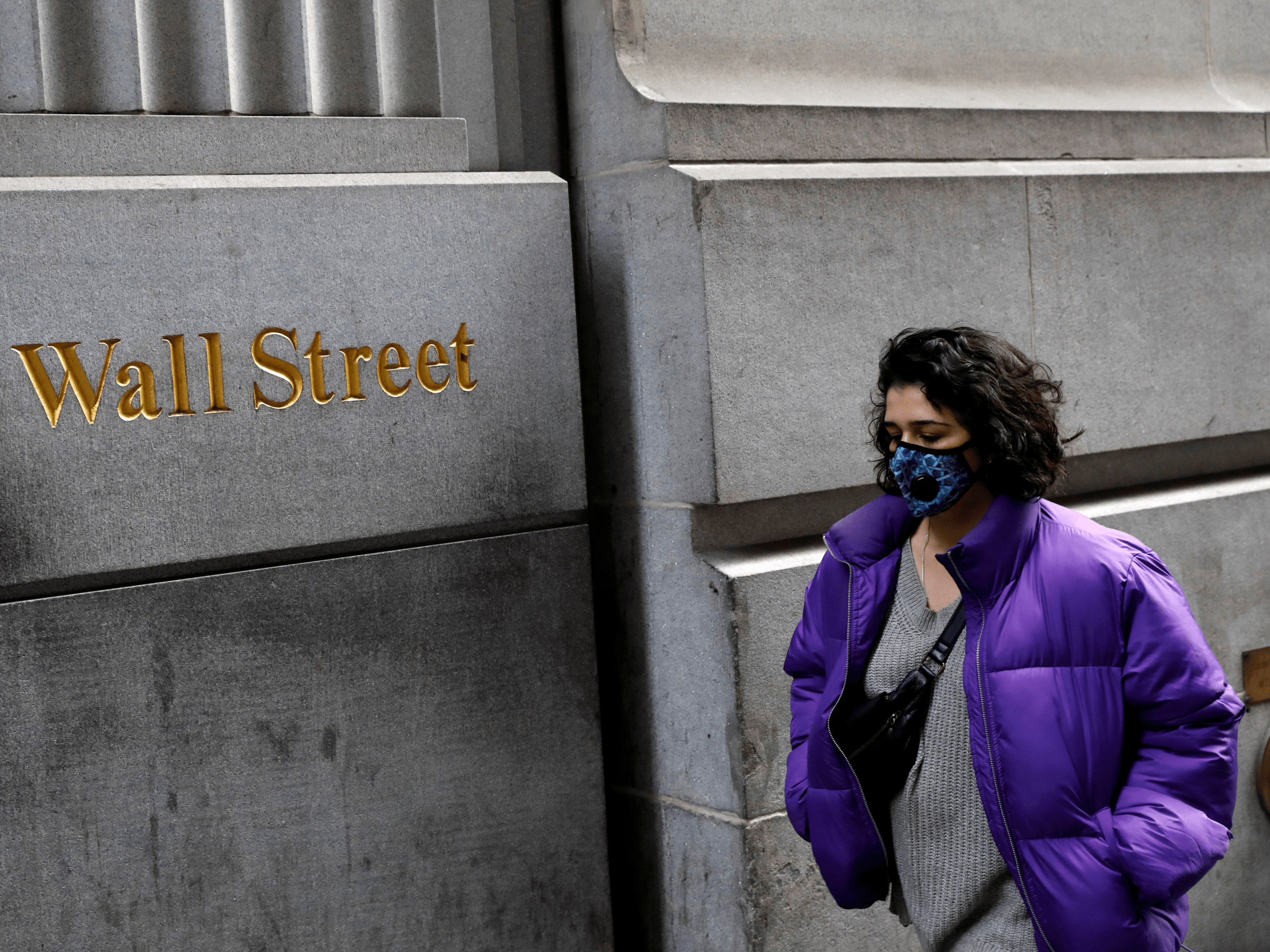 FILE PHOTO: A person wearing a face mask walks along Wall Street after further cases of coronavirus were confirmed in New York City, New York, U.S., March 6, 2020. REUTERS/Andrew Kelly/File Photo
