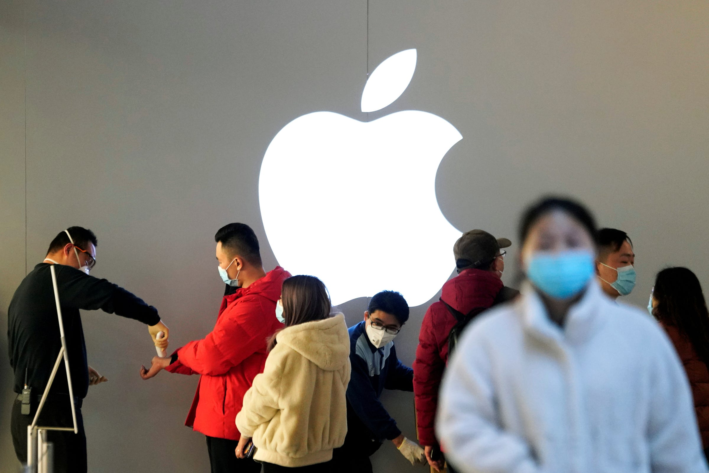 FILE PHOTO: People wearing protective masks wait for checking their temperature in an Apple Store, in Shanghai, China, as the country is hit by an outbreak of the novel coronavirus, February 21, 2020. REUTERS/Aly Song
