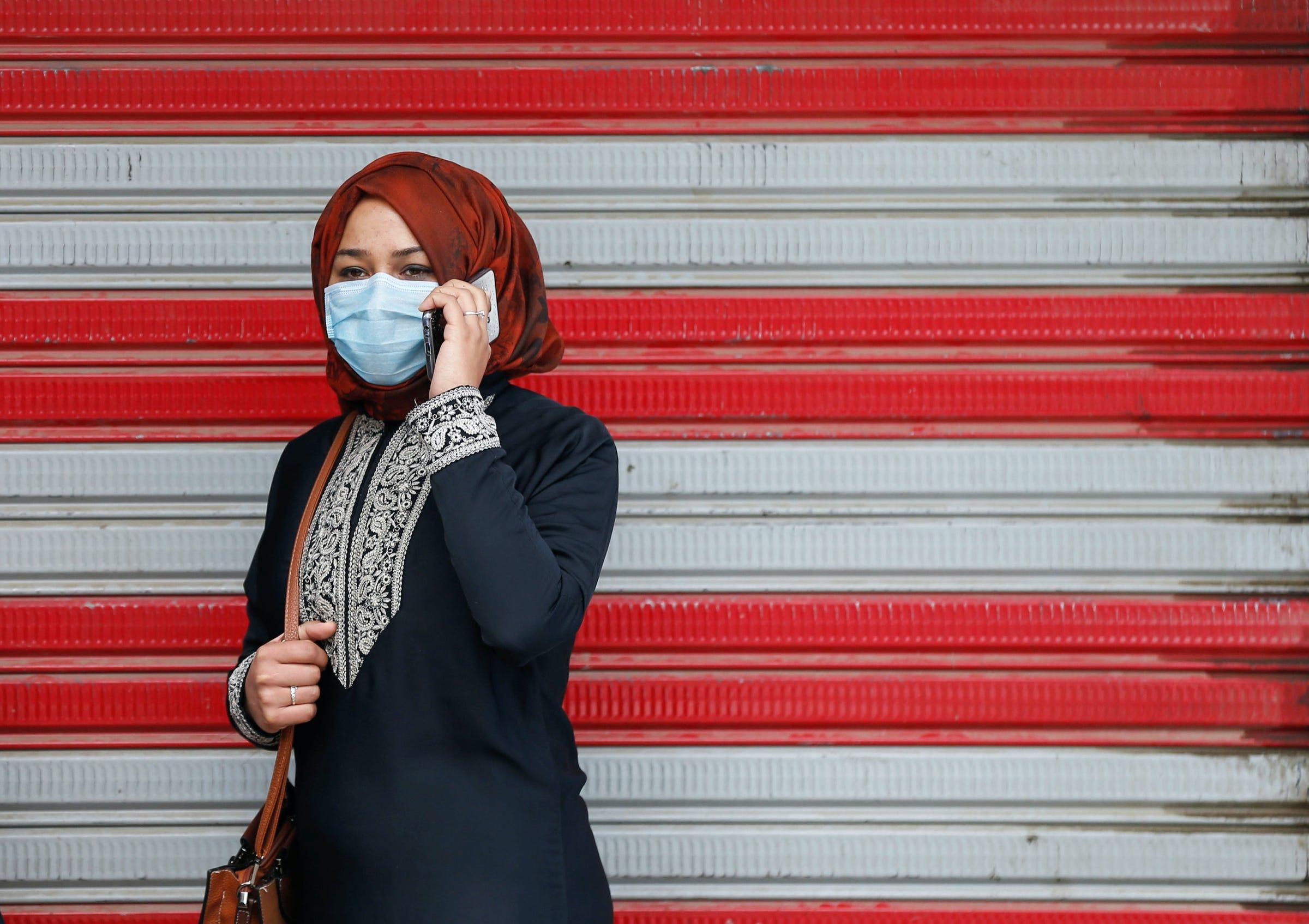 woman mobile cell phone coronavirus covid 19 surgical face mask kabul afghanistan red white background 2020 03 29T095012Z_1762391908_RC2LTF96UYPF_RTRMADP_3_HEALTH CORONAVIRUS AFGHANISTAN.JPG