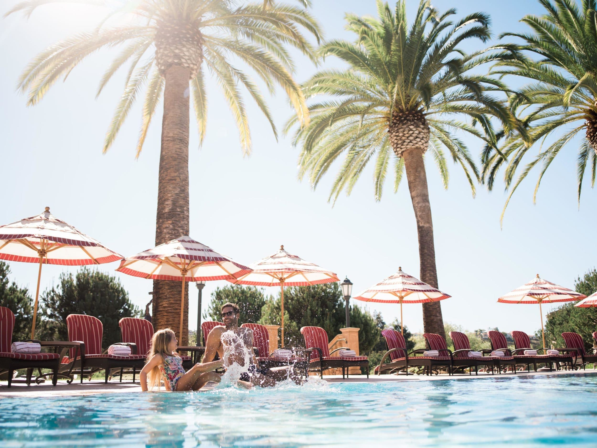 A girl splashes in the main swimming pool with her father at Fairmont Grand Del Mar, my top pick for kid-friendly hotels in San Diego.