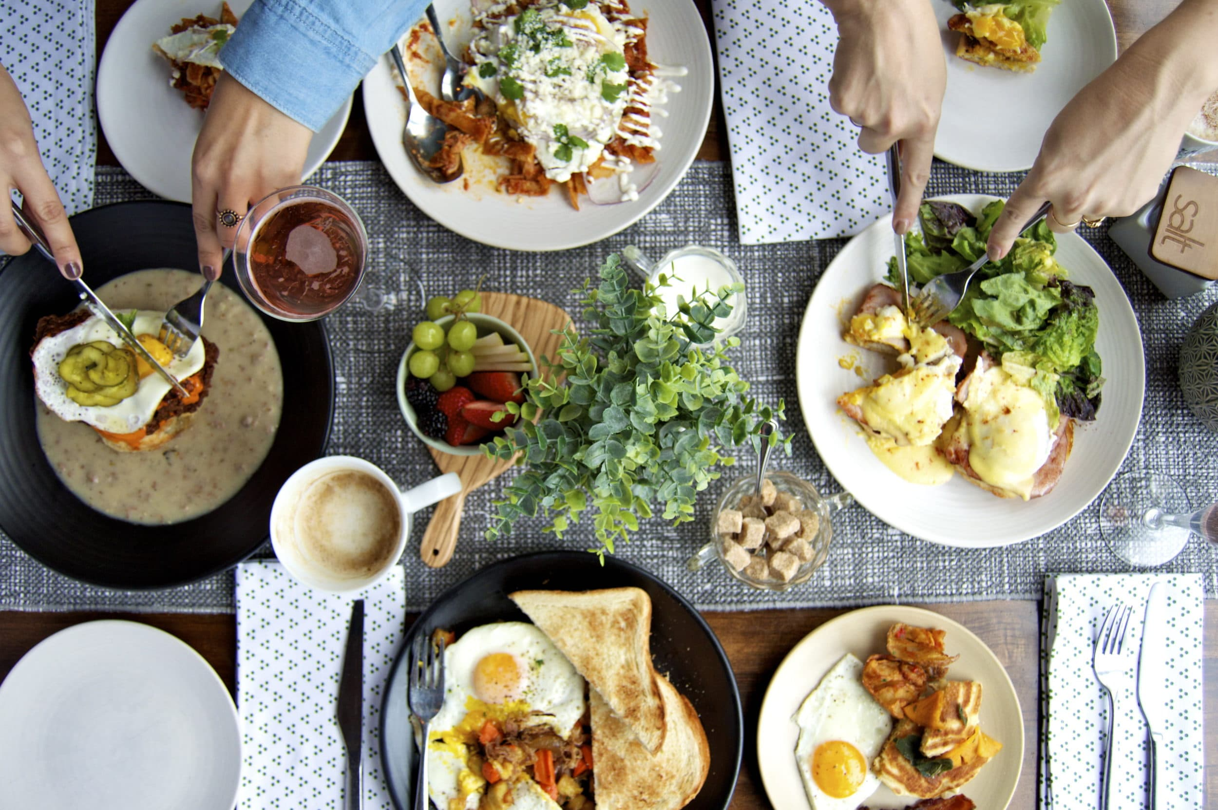 Top-down photo of people eating brunch items at Whisknladle La Jolla restaurant.