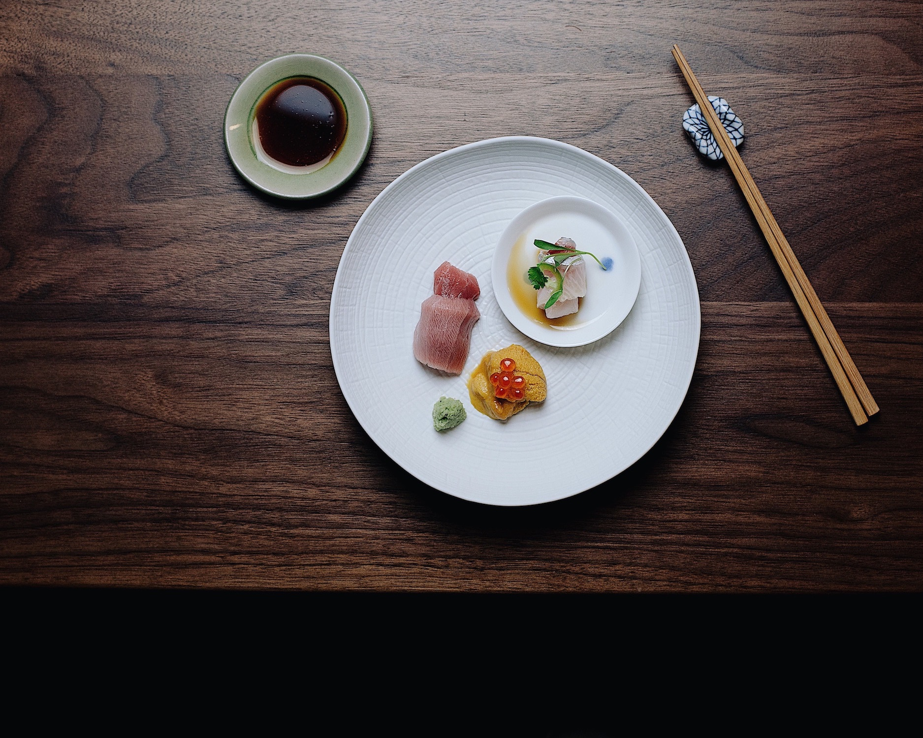 Delicate sashimi on a large white plate on a table at Himitsu.