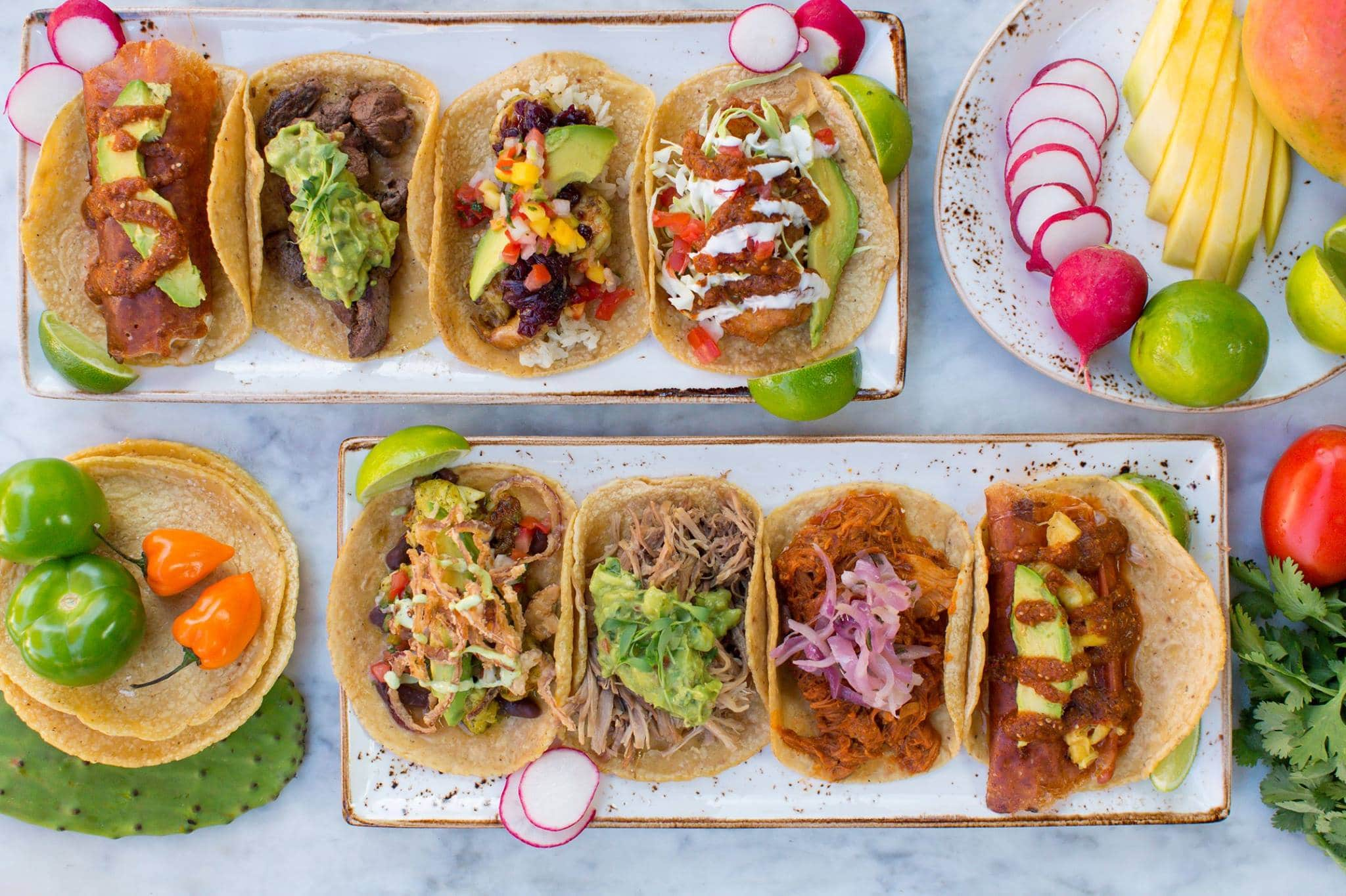 Top-down photo of eight different Puesto tacos.