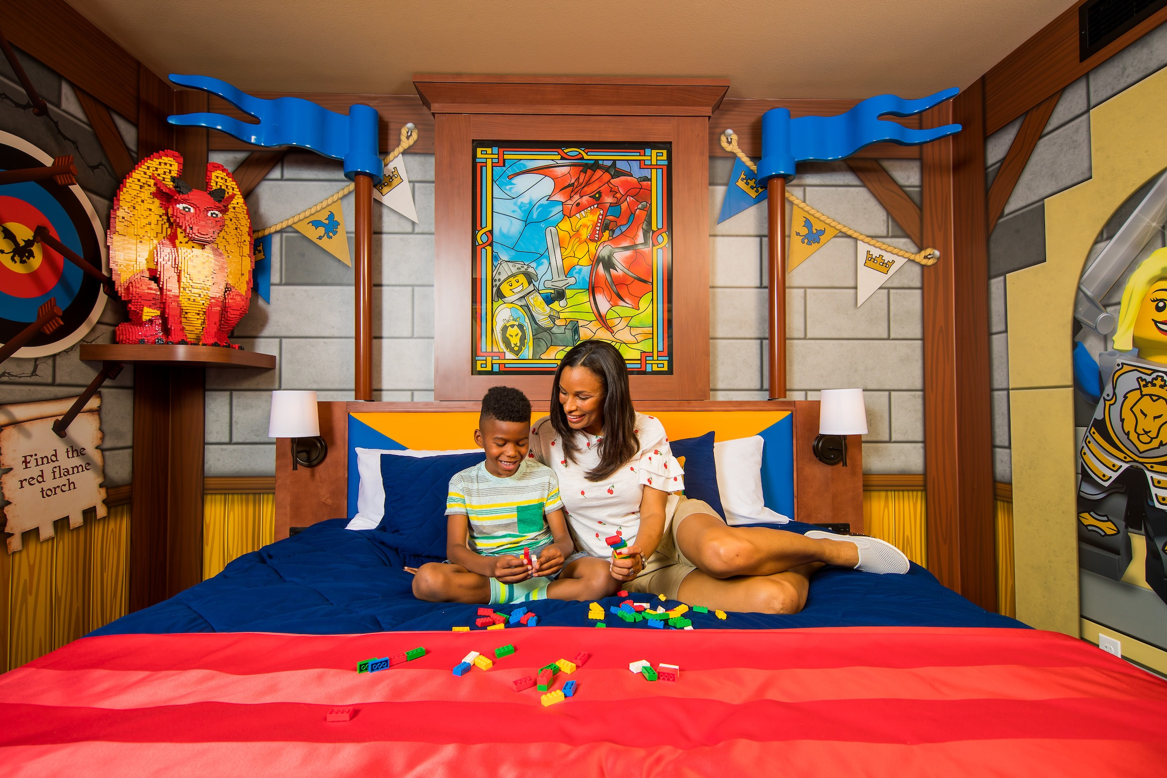 A mom and son play LEGOs on the bed in a Knight Room at LEGOLAND Castle Hotel, a popular San Diego family hotel.