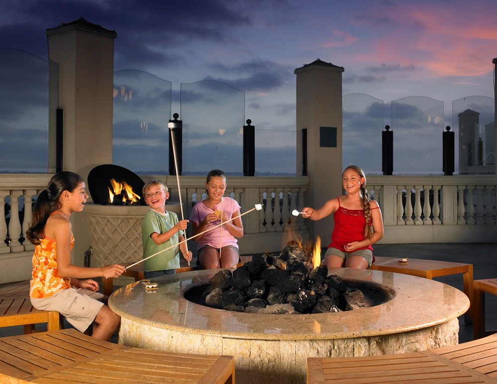 Kids roast s'mores on an outdoor fire pit at Manchester Grand Hyatt San Diego.