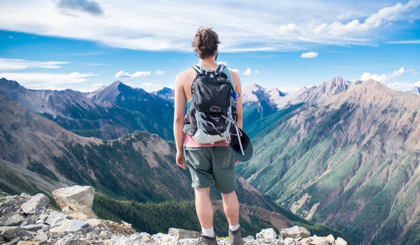 A solo backpacker standing on a cliff looking at the scenery
